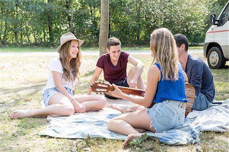 Group of young adults sitting on picnic blanket , young woman playing guitar Stock Photo - Premium Royalty-Free, Code: 649-08328216
