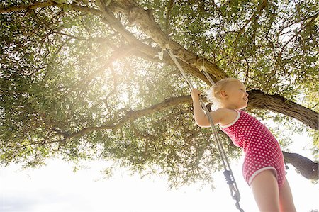 spotted - Low angle view of female toddler standing on tree swing Stock Photo - Premium Royalty-Free, Code: 649-08328692