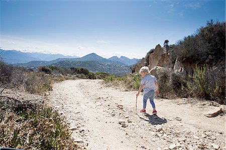 Female toddler on dirt track with walking stick, Calvi, Corsica, France Stock Photo - Premium Royalty-Free, Code: 649-08328702