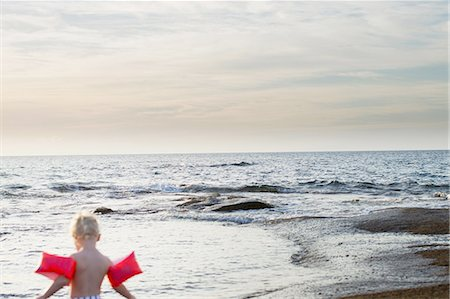 Rear view of female toddler wearing inflatable armbands at coast, Calvi, Corsica, France Stock Photo - Premium Royalty-Free, Code: 649-08328720