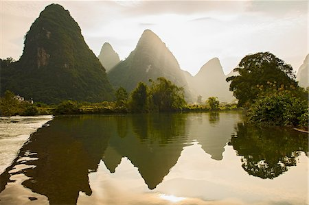 Mirror image of mountains in Li river at sunset, Yangshuo, Guangxi Zhuang, China Stock Photo - Premium Royalty-Free, Code: 649-08328940