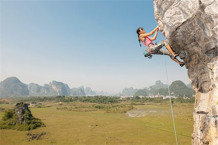 dangling - Female climber hanging from the Egg - a limestone cliff in Yangshuo, Guangxi Zhuang, China Stock Photo - Premium Royalty-Free, Code: 649-08329054