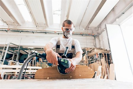 Man sanding skateboard in workshop Stock Photo - Premium Royalty-Free, Code: 649-08329151