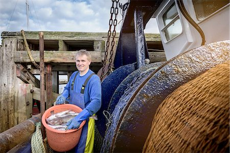 Fisherman with nets on stern of trawler, portrait Stock Photo - Premium Royalty-Free, Code: 649-08381005