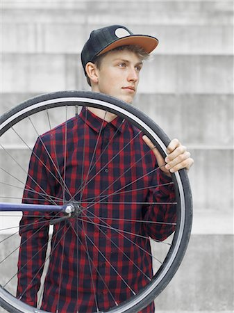sports - Urban cyclist carrying tyre in front of steps Stock Photo - Premium Royalty-Free, Code: 649-08381017
