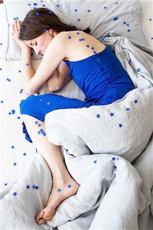 Overhead view of mature woman wearing blue pyjamas lying curled up in bed covered in stars Stock Photo - Premium Royalty-Free, Code: 649-08381055
