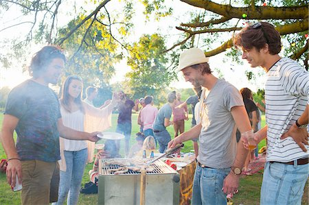Happy adult friends barbecuing at sunset party in park Stock Photo - Premium Royalty-Free, Code: 649-08381087
