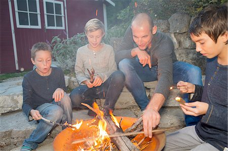 Father and three sons sitting by garden campfire at dusk Stock Photo - Premium Royalty-Free, Code: 649-08381247