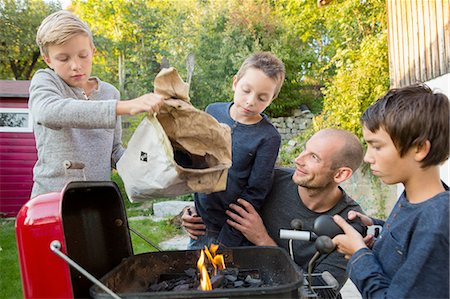 Mid adult man and sons preparing barbecue in garden Stock Photo - Premium Royalty-Free, Code: 649-08381240