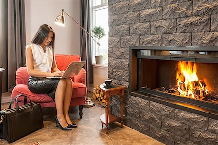 Business woman working using laptop, sitting next to fireplace in hotel lobby Stock Photo - Premium Royalty-Free, Code: 649-08381408