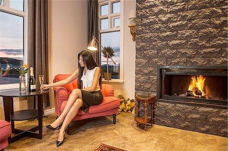Business woman drinking champagne, sitting next to fireplace in hotel lobby Stock Photo - Premium Royalty-Free, Code: 649-08381412
