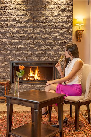 Business woman drinking champagne, sitting next to fireplace in hotel lobby Stock Photo - Premium Royalty-Free, Code: 649-08381413