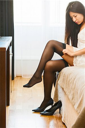 Mid adult woman sitting on edge of bed, putting on stockings Stock Photo - Premium Royalty-Free, Code: 649-08381423