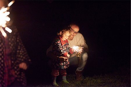 Father crouching next to daughter holding sparkler Stock Photo - Premium Royalty-Free, Code: 649-08381542