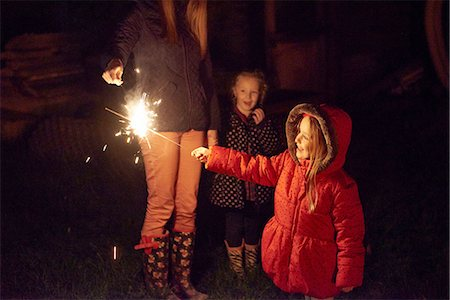 Side view of girl wearing red fur trim coat holding sparkler being ignighted by mother, smiling Stock Photo - Premium Royalty-Free, Code: 649-08381543