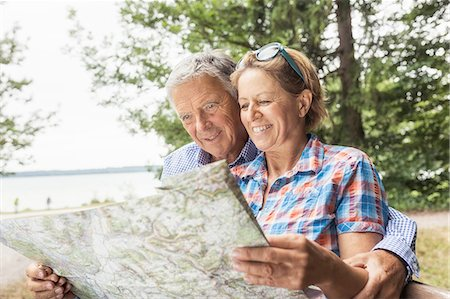 Couple in forest, looking at map, smiling Stock Photo - Premium Royalty-Free, Code: 649-08381585