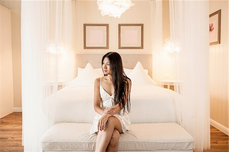 Beautiful woman wearing negligee sitting in front of bed in hotel suite Stock Photo - Premium Royalty-Free, Code: 649-08381753