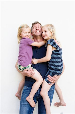 Portrait of mature man carrying two young daughters in front of white wall Stock Photo - Premium Royalty-Free, Code: 649-08422508