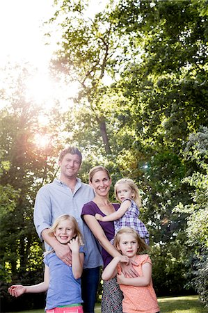 Portrait of parents and three young daughters in sunlit park Stock Photo - Premium Royalty-Free, Code: 649-08422521