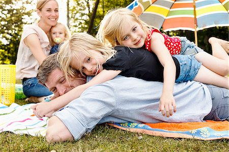 Two daughters lying on top of father at family picnic in park Stock Photo - Premium Royalty-Free, Code: 649-08422561