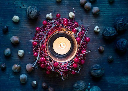 Overhead view of burning candle surrounded by berry wreath and nuts Stock Photo - Premium Royalty-Free, Code: 649-08422666