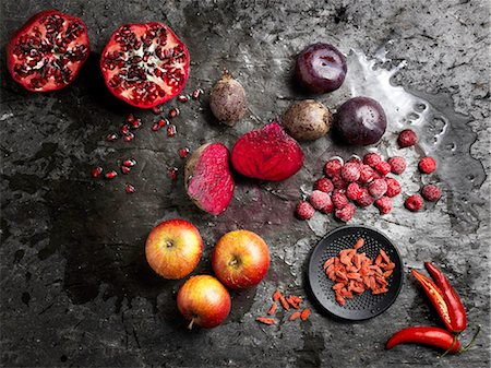 delicious - Overhead view of halved red fruit and vegetables on dark background Stock Photo - Premium Royalty-Free, Code: 649-08422900