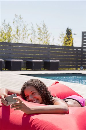 Girl lying on poolside cushion reading smartphone, Cassis, Provence, France Stock Photo - Premium Royalty-Free, Code: 649-08422956