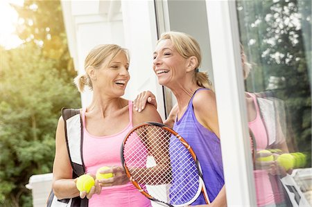 Two mature women preparing to play tennis at patio door Stock Photo - Premium Royalty-Free, Code: 649-08423216