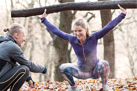 Young woman crouching arms raised, holding tree branch exercising, smiling Stock Photo - Premium Royalty-Free, Code: 649-08423326