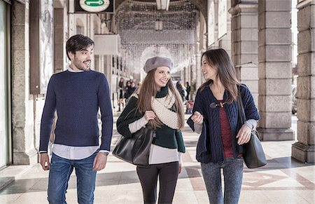 Front view of friends walking side by side in shopping mall smiling Stock Photo - Premium Royalty-Free, Code: 649-08479393