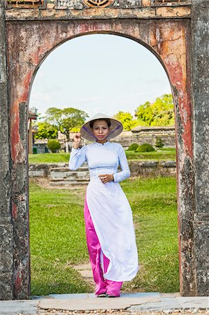 Mid adult woman standing in archway wearing ao dai and conical hat looking at camera, Hue, Vietnam Stock Photo - Premium Royalty-Free, Code: 649-08479543