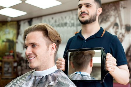 Barber using mirror to show smiling customer haircut Stock Photo - Premium Royalty-Free, Code: 649-08479647