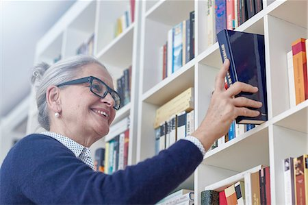 selecting - Grey haired mature woman selecting book from bookshelves Stock Photo - Premium Royalty-Free, Code: 649-08479795