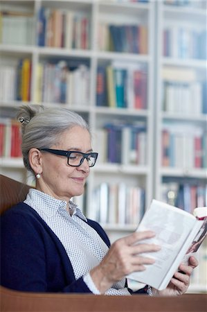 Grey haired mature woman reading book from bookshelves Stock Photo - Premium Royalty-Free, Code: 649-08479797
