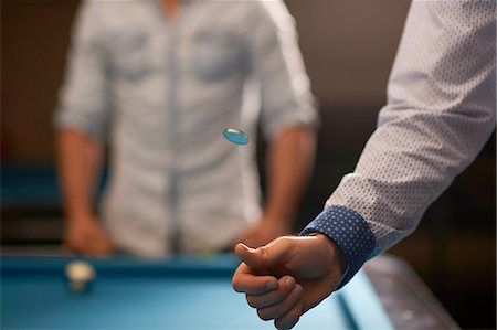 Man tossing coin at pool table Stock Photo - Premium Royalty-Free, Code: 649-08480187