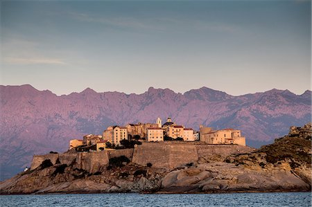 View of sea and Calvi on headland at dusk, Corsica, France Stock Photo - Premium Royalty-Free, Code: 649-08480367