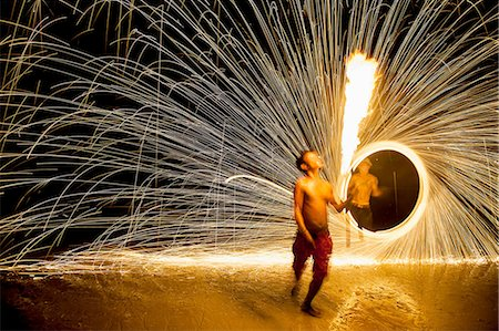spark - Young man displaying a fire poi show on the beach, Koh Samet, Thailand Stock Photo - Premium Royalty-Free, Code: 649-08480374