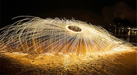 flexible (people or objects with physical bendability) - Young man displaying a fire poi show on the beach, Koh Samet, Thailand Stock Photo - Premium Royalty-Free, Code: 649-08480373