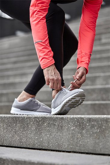 Cropped shot of mature woman training on city stairway, tying trainer laces Stock Photo - Premium Royalty-Free, Image code: 649-08544126