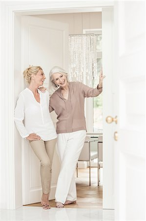 Mother and daughter standing together at home, laughing Stock Photo - Premium Royalty-Free, Code: 649-08548684