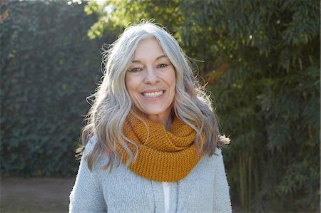 portrait - Portrait of woman with long gray hair looking at camera smiling Stock Photo - Premium Royalty-Free, Code: 649-08548953