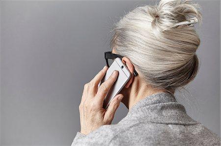 Grey haired woman using smartphone to make telephone call Stock Photo - Premium Royalty-Free, Code: 649-08549358