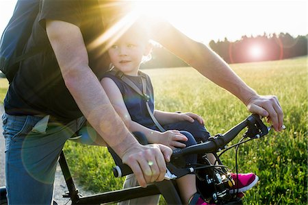 Father and baby daughter riding bike together, mid section Stock Photo - Premium Royalty-Free, Code: 649-08543165