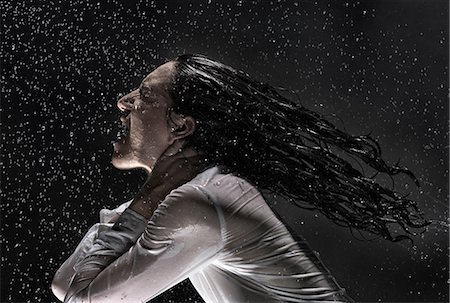 Side view of woman wearing white shirt drenched in rain throwing back hair Stock Photo - Premium Royalty-Free, Code: 649-08543282