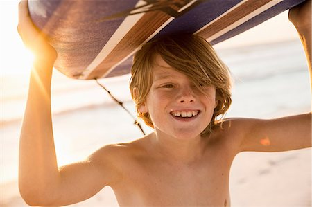 Boy carrying surfboard over head smiling Stock Photo - Premium Royalty-Free, Code: 649-08543789