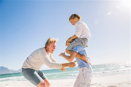 Big brother on beach carrying brother on shoulders, father tickling Stock Photo - Premium Royalty-Free, Code: 649-08543811