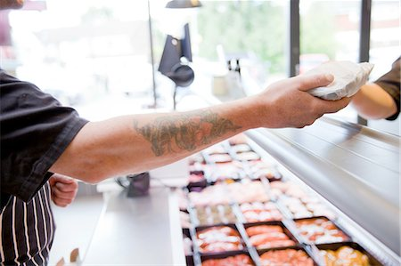 Cropped shot of butcher handing produce to customer in butchers shop Stock Photo - Premium Royalty-Free, Code: 649-08565944