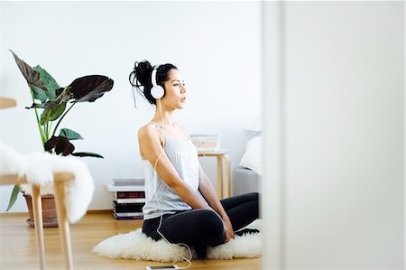 Young woman practicing yoga in living room whilst listening to headphones Stock Photo - Premium Royalty-Free, Code: 649-08565969