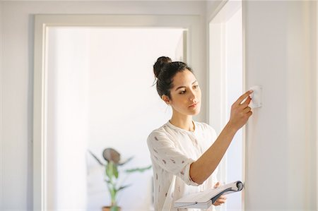 Young woman adjusting central heating control at home Stock Photo - Premium Royalty-Free, Code: 649-08565975