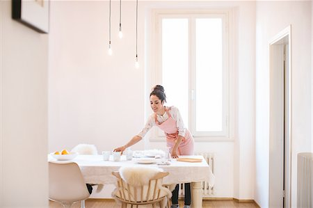 Young housewife wearing apron preparing dining table Stock Photo - Premium Royalty-Free, Code: 649-08565976